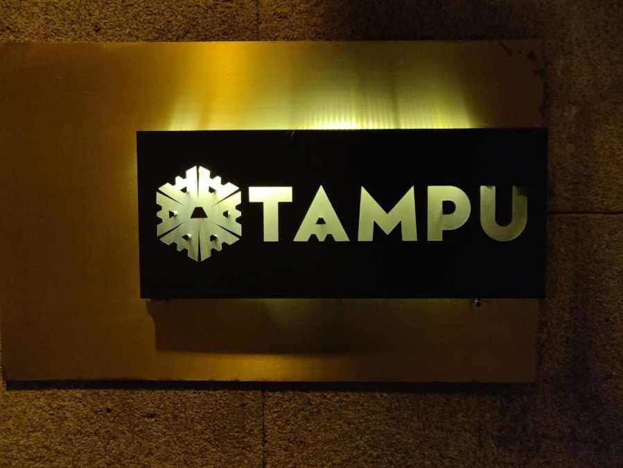 Logotipo de Tampu en la entrada Cartel iluminado con luz blanca por detrás, fondo negro y letras mayusculas que dejan pasar la luz