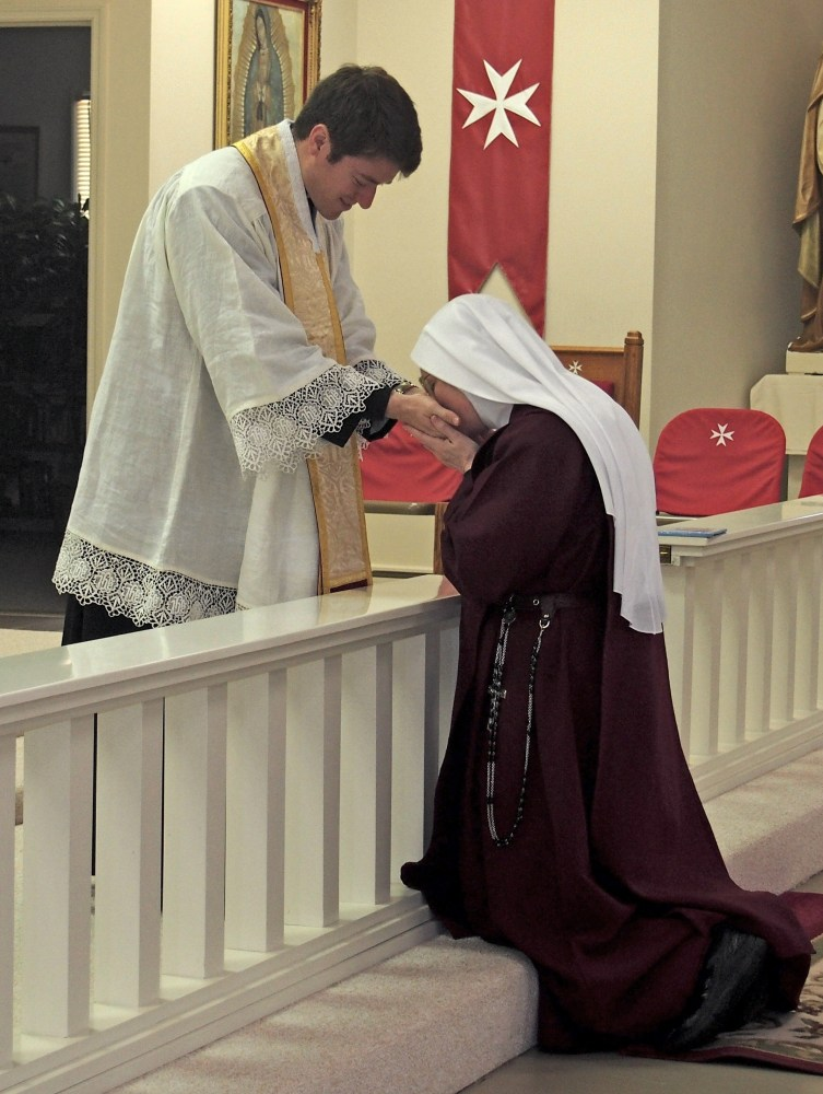 Mother Marietta receives Father Hendershott's priestly blessing and kisses his anointed hands.
