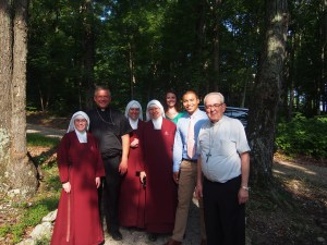 Bishop Stika, Cardinal Rigali, Handmaids and Frassati friends walking the grounds near the lodge.