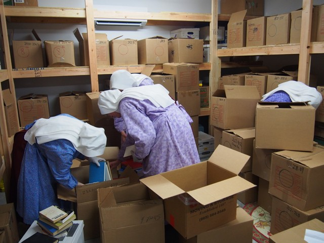 Handmaids sort books for eventual placement.
