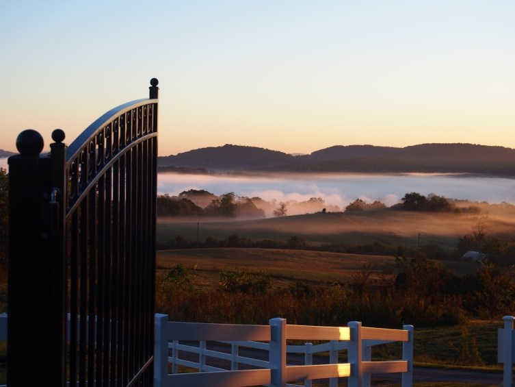 The morning sun lights up the Holston river fog and our gate and fence.
