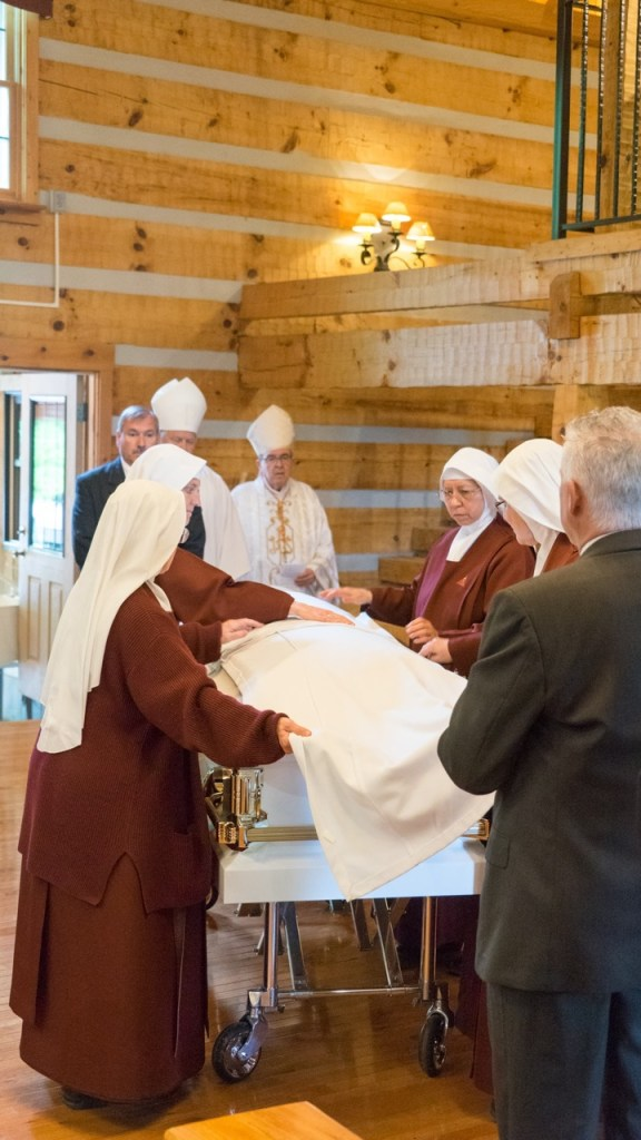 After Mass, Handmaids remove the funeral pall.