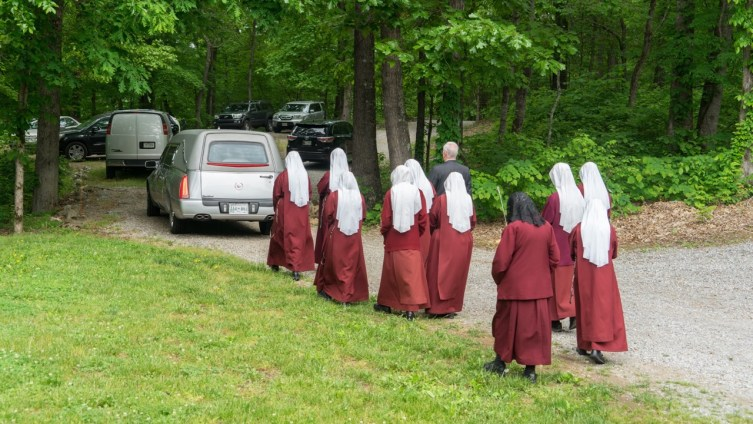 Handmaids walk behind the hearse, following Sister Mel Pierre, to her final resting place on earth.