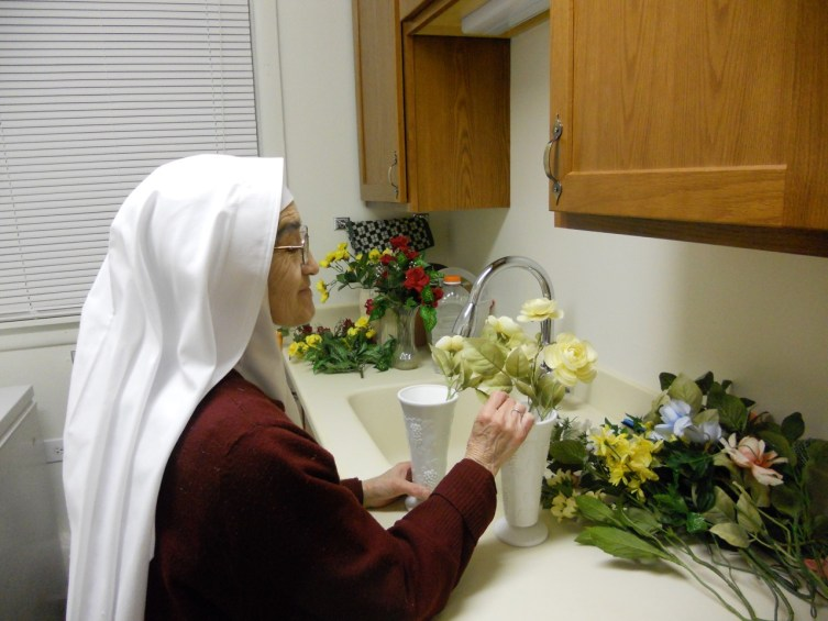 Sister is dedicated gardener as well as a sacristan able to arrange both live and artificial flowers in a pinch.