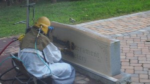 A workman sandblasts the main headstone in our cemetery.