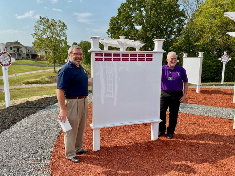 After plenty of sweat-equity, including some blood and tears, Knights Jimmy Dee and Ron Henry happily pose beside the initial set of priest names to be placed in the garden.
