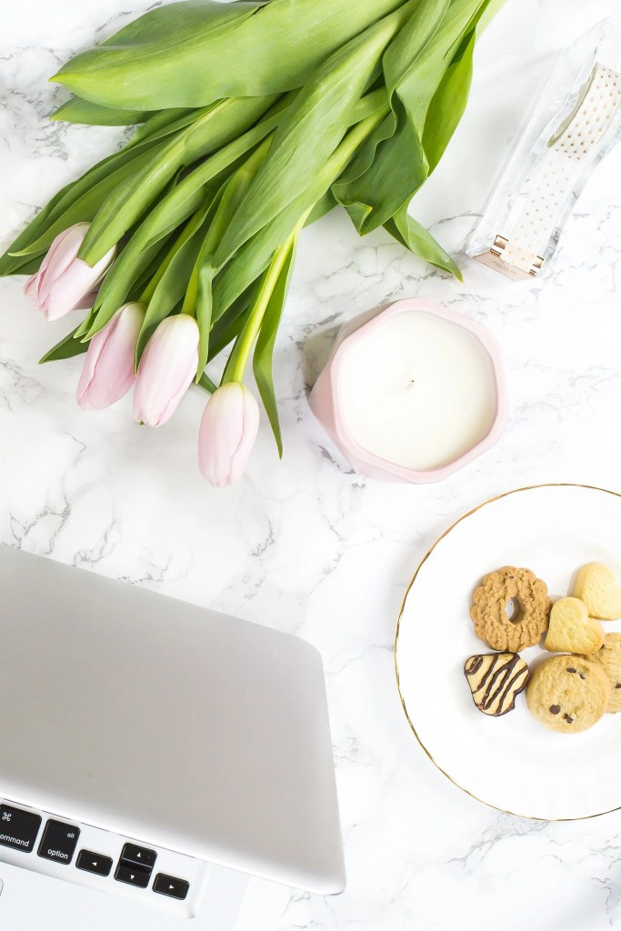 A blush styled desktop featuring a laptop.