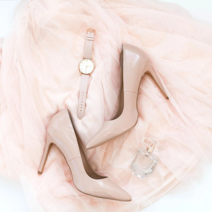 Flatlay of pink tulle skirt, pink heels, pink watch, and perfume bottle.
