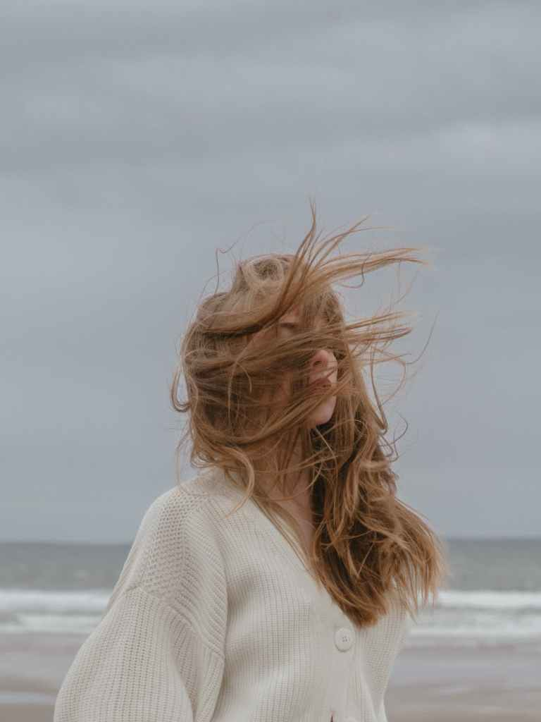 dreamy young woman with windy hair recreating on seashore against cloudy sky