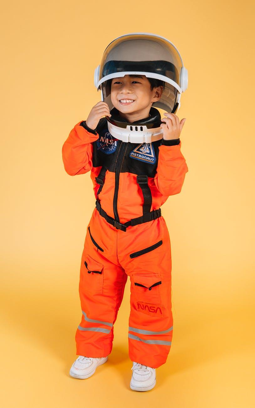 expressive asian boy wearing cosmonaut costume