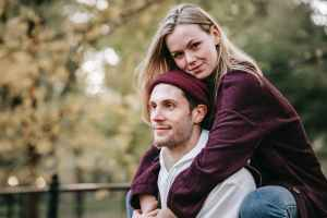 smiling man giving sincere girlfriend piggyback ride in park