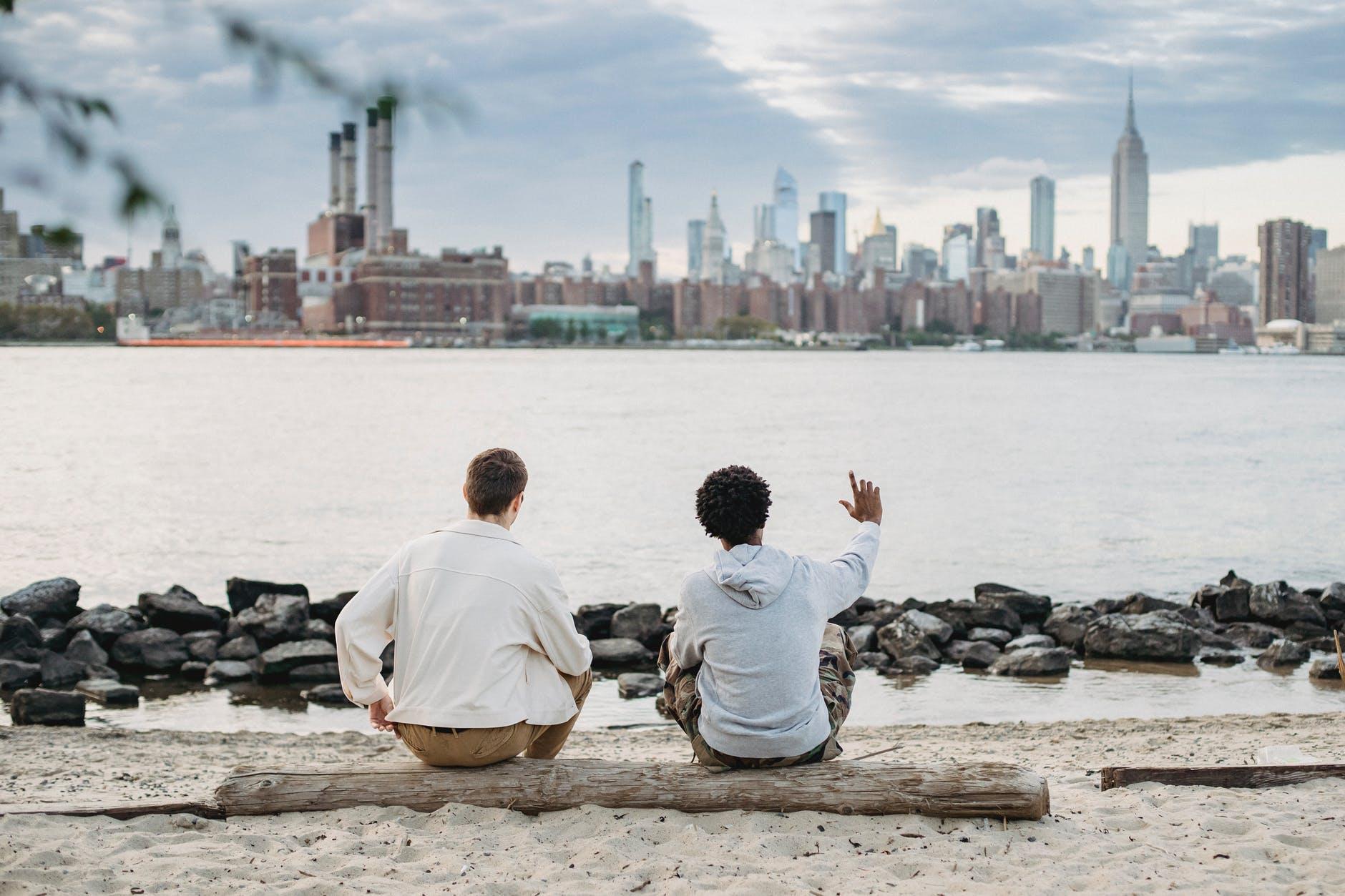 unrecognizable diverse friends sitting on bank of river against cityscape