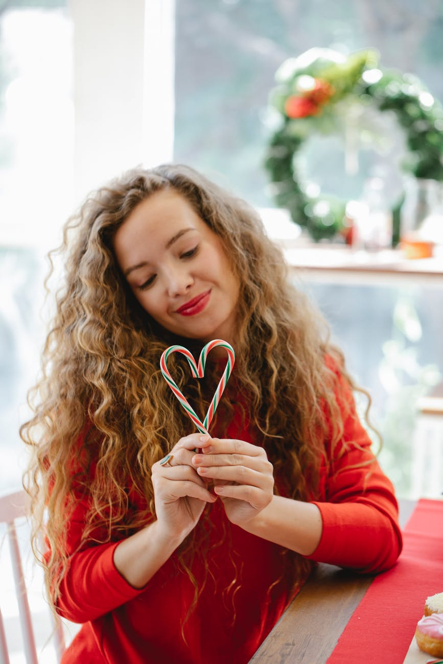 curly woman with candy canes in hands