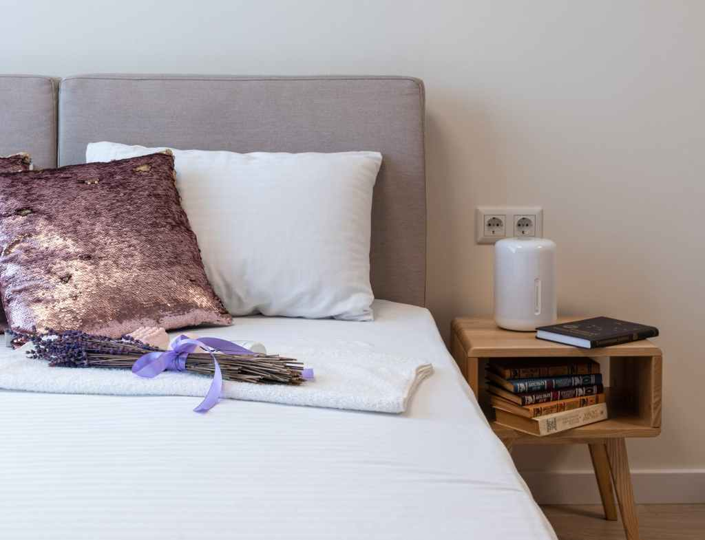 lavender bouquet placed on bed in cozy bedroom in sunny morning