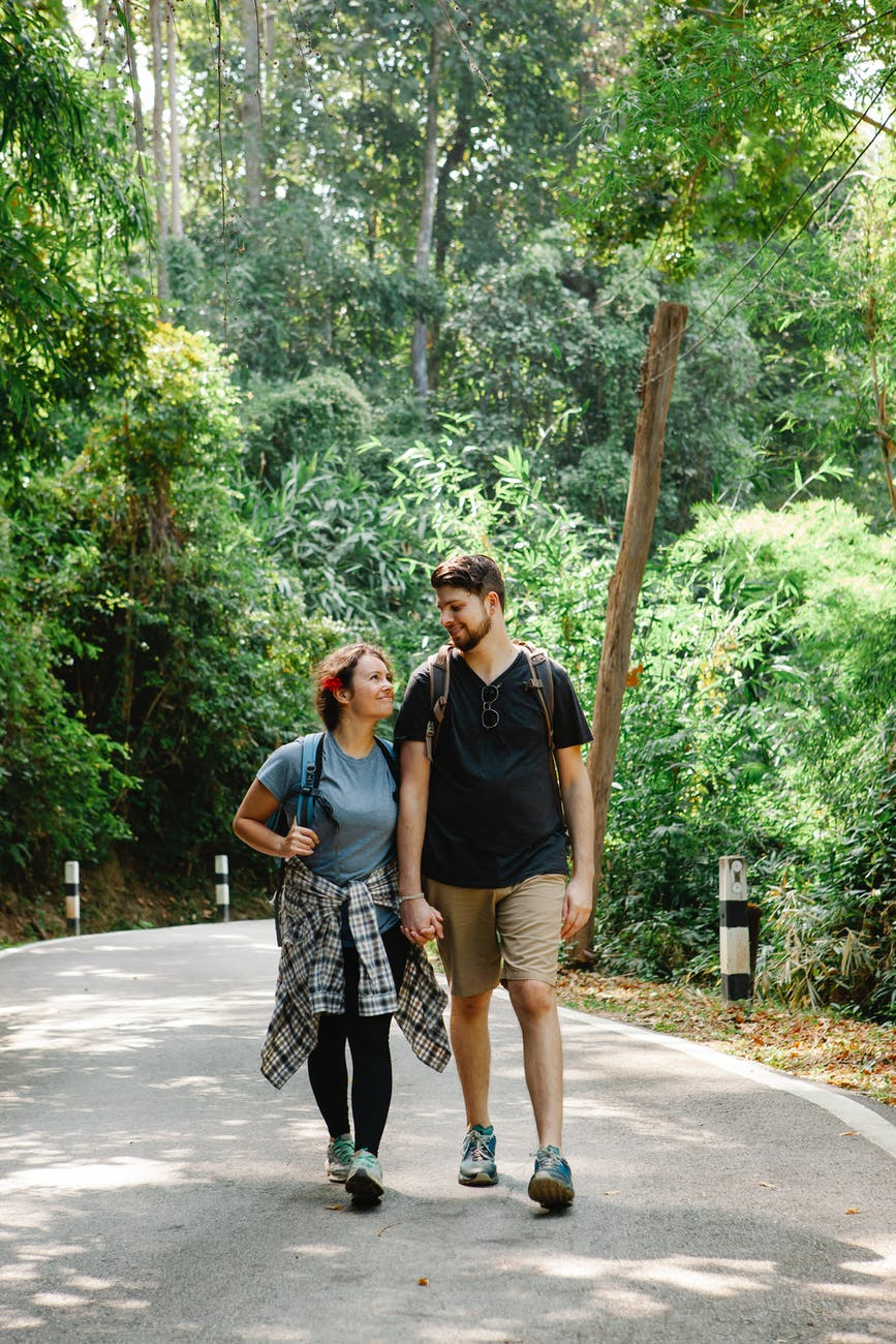 romantic couple holding hands and walking on path in jungle