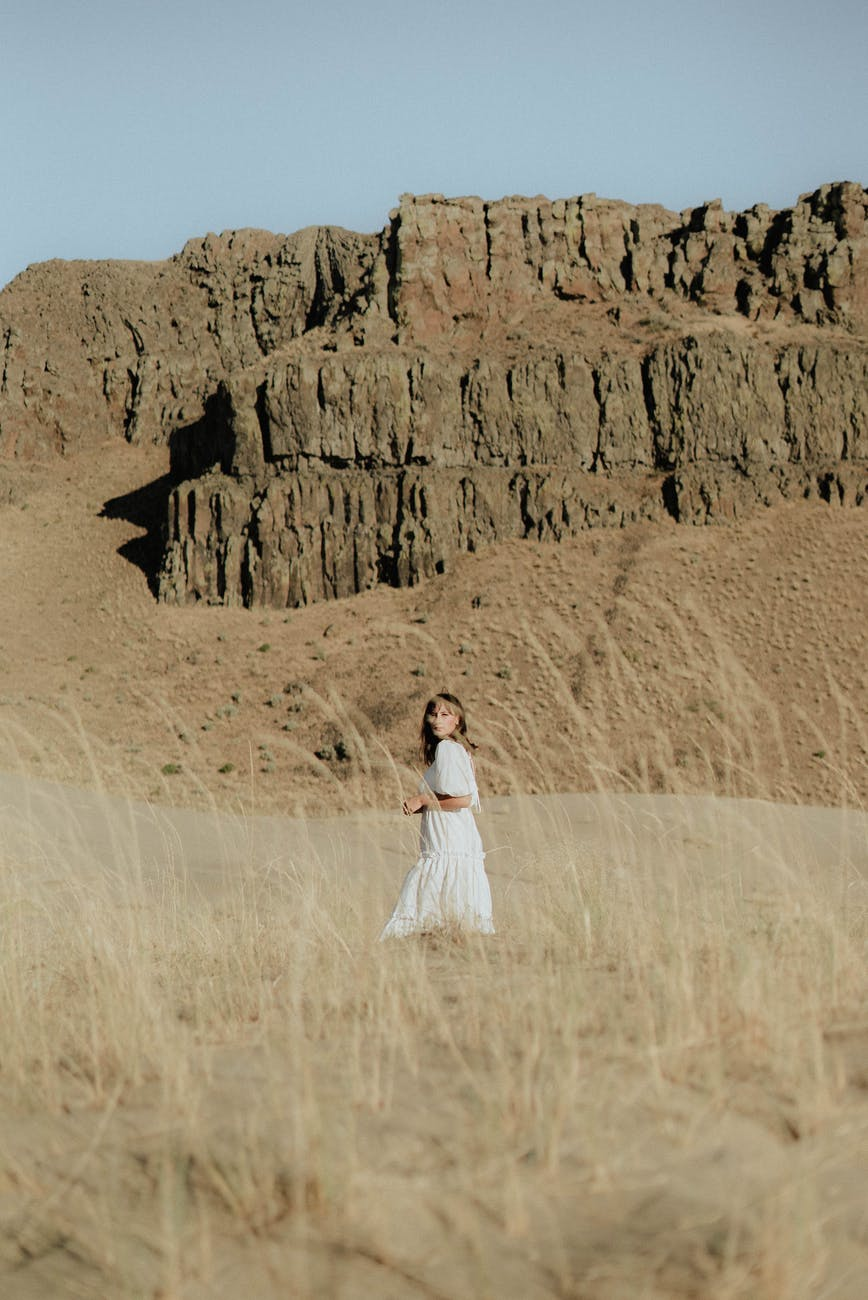 woman in light dress standing on sand against rocky terrain