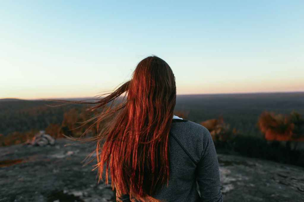 anonymous woman on mountain enjoying view of valley with woods