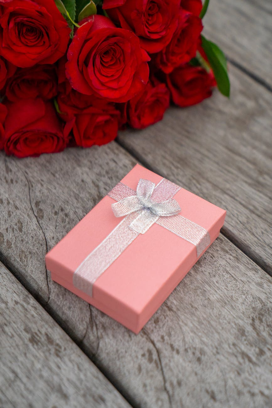 gift box and flowers on wooden surface