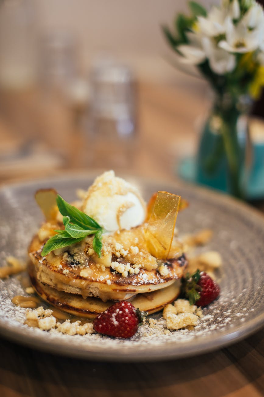 delicious pancakes with ice cream and nuts decorated with strawberries