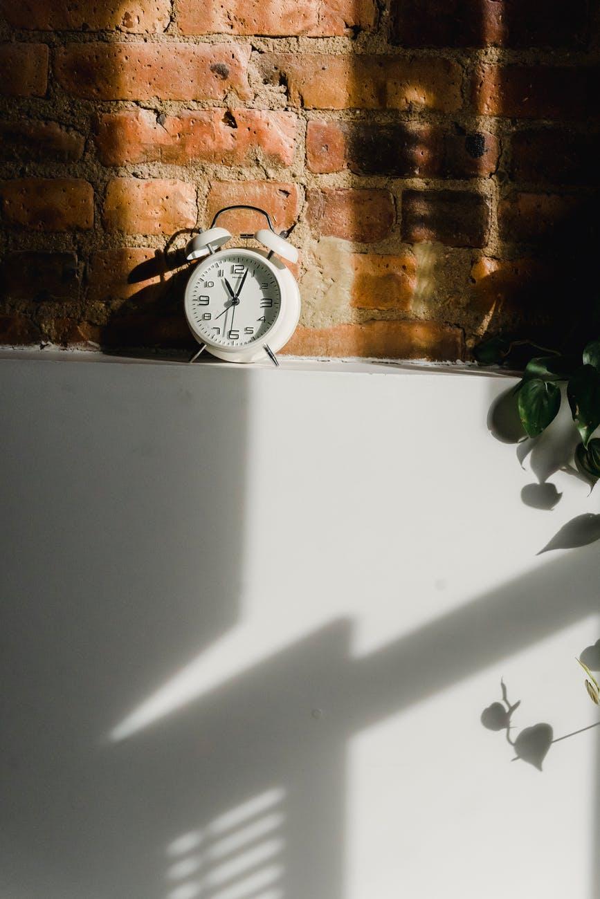 alarm clock on white cupboard near brick wall