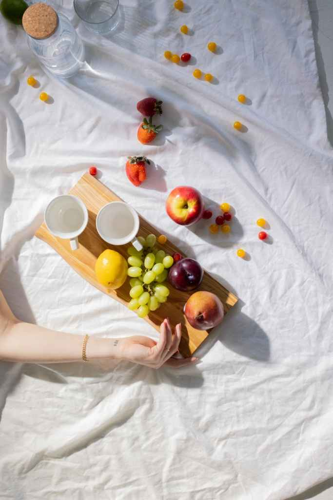 faceless woman lying on blanket near ripe colorful fruits