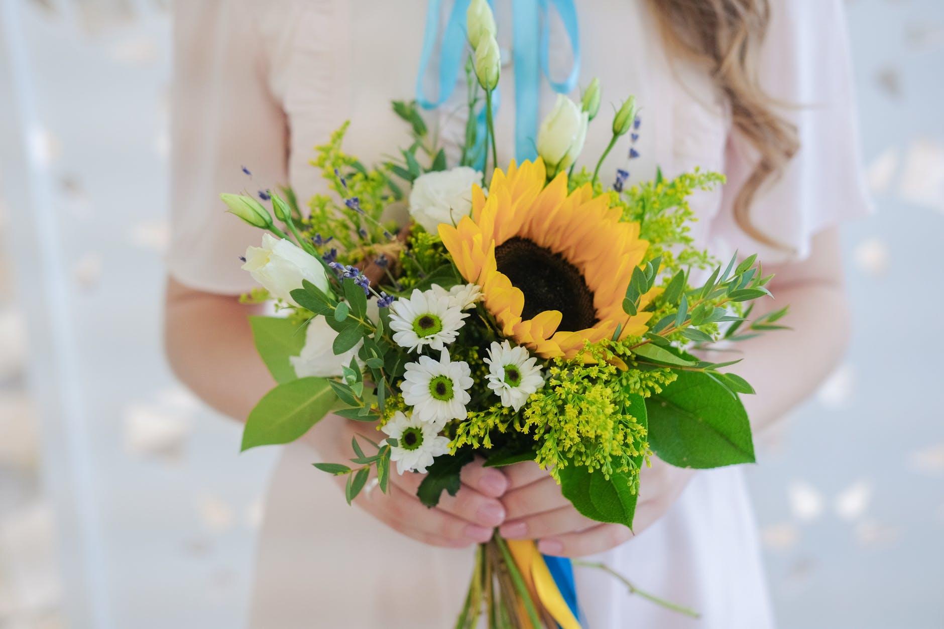 bunch of fresh elegant flowers in hands of crop unrecognizable bride