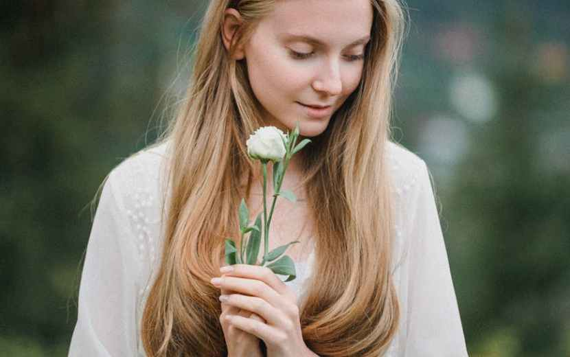 dreamy stylish lady with flower in hands standing on grassy meadow in highland