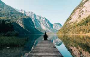 person on a bridge near a lake