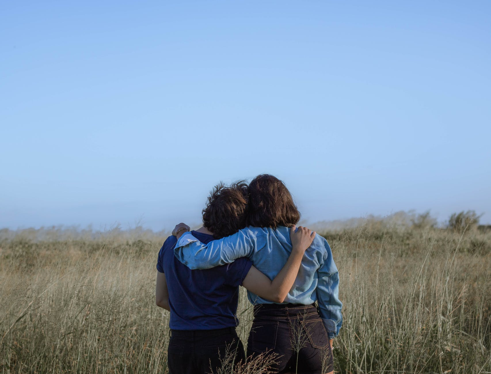 anonymous female friends embracing on spacious meadow