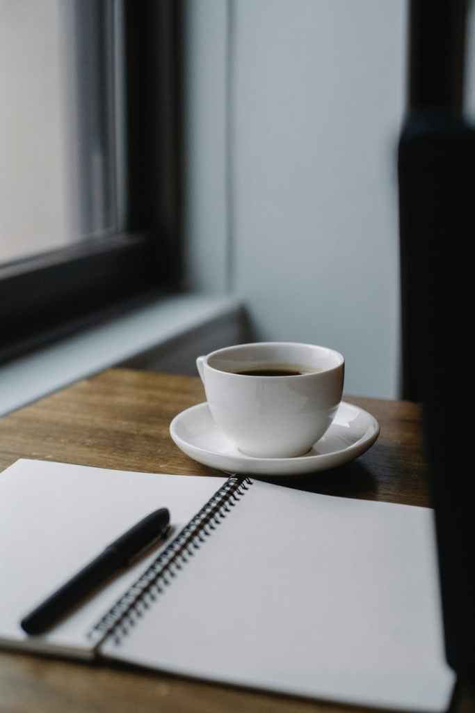 cup of coffee served on table with notepad and pen