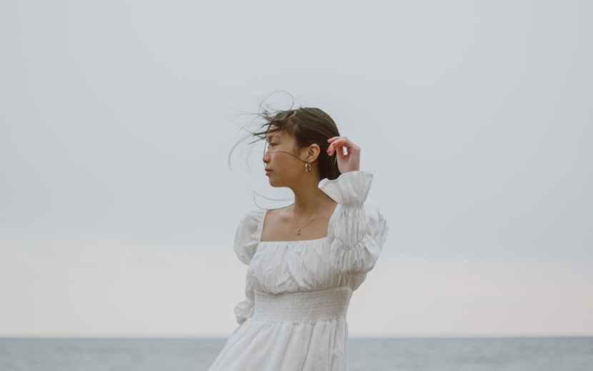 gentle asian traveler in white dress contemplating sea