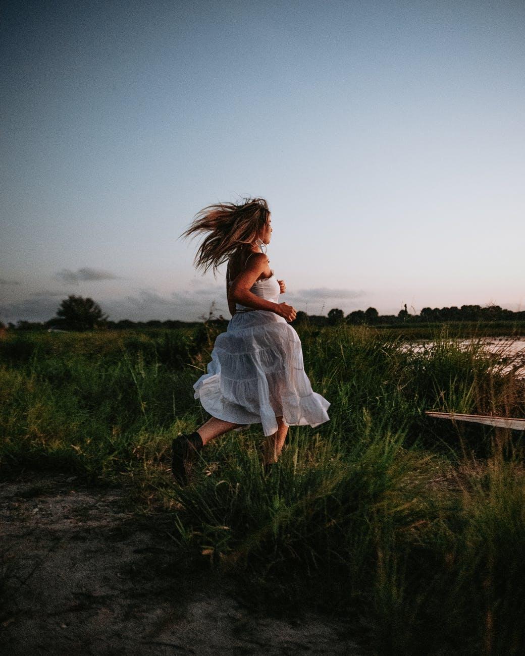 woman in summer dress running through grass to pond