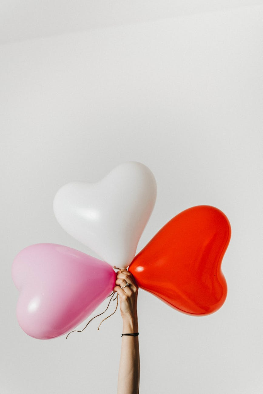 crop woman with heart shaped balloons