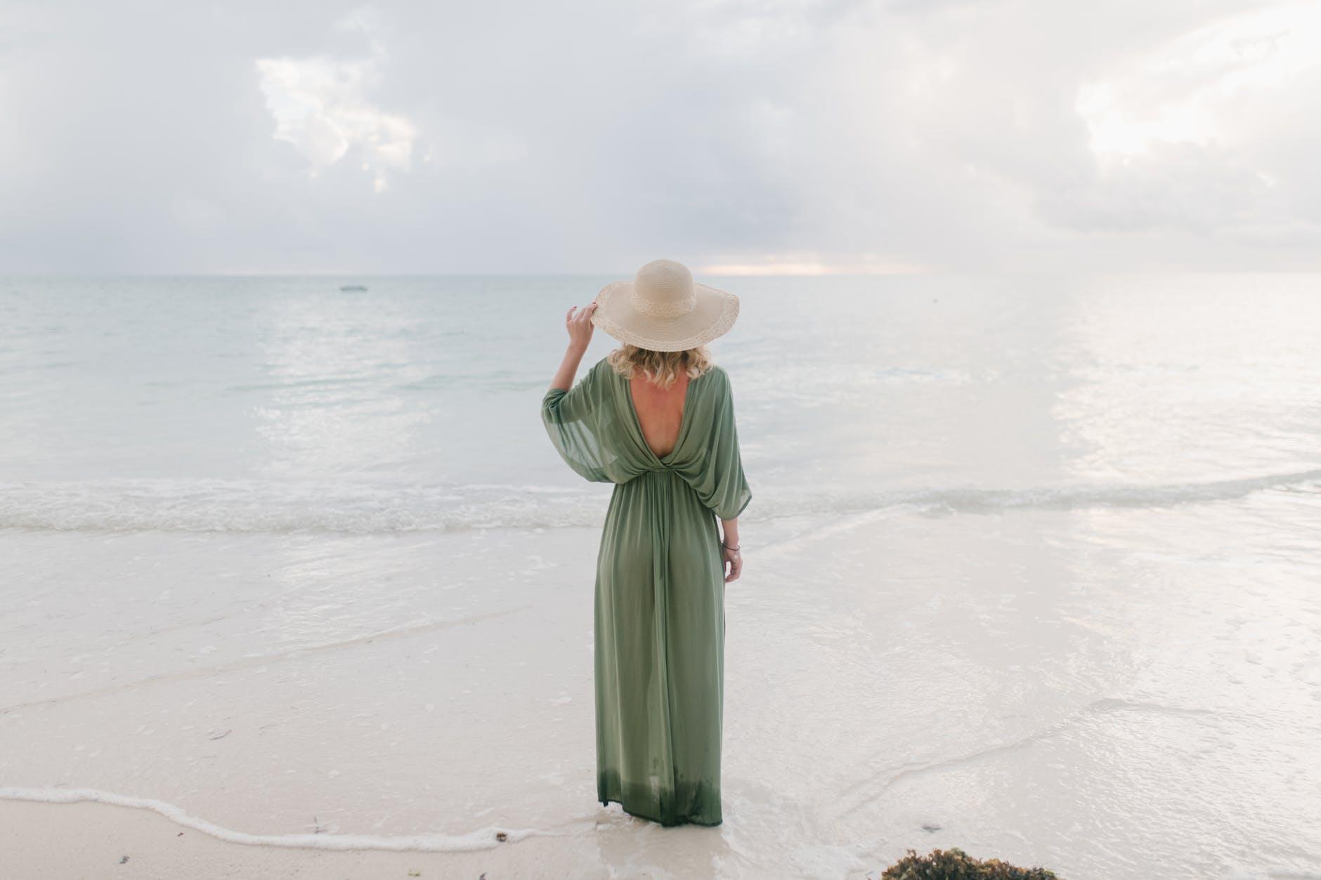 anonymous woman standing on wet beach near sea