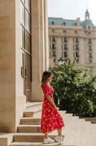 a woman in floral dress posing on the steps of a building