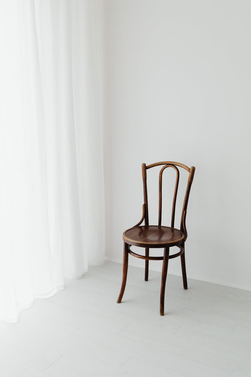 brown wooden chair beside white curtain