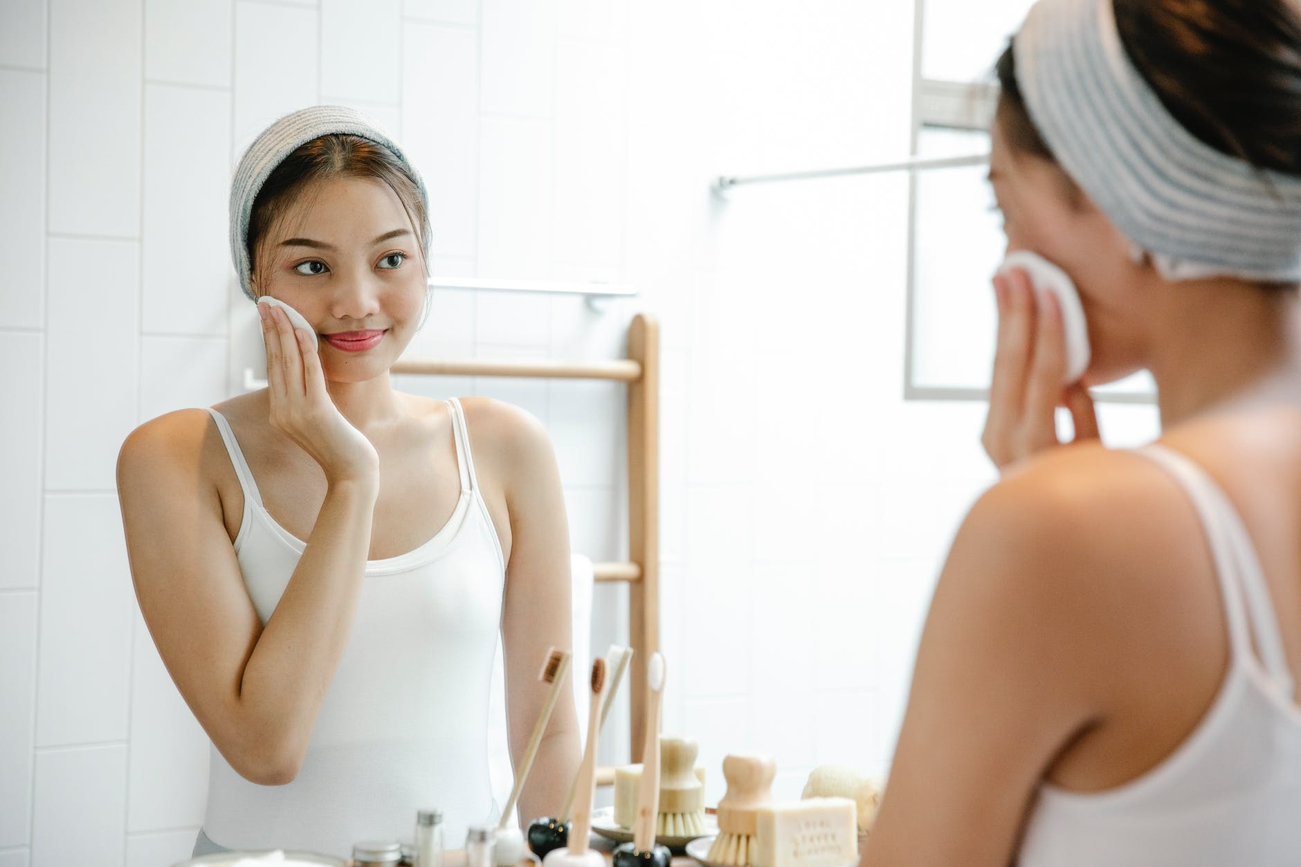 content asian woman cleaning face with cotton pad