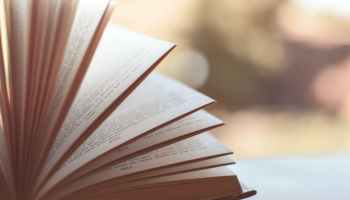 book opened on white surface selective focus photography