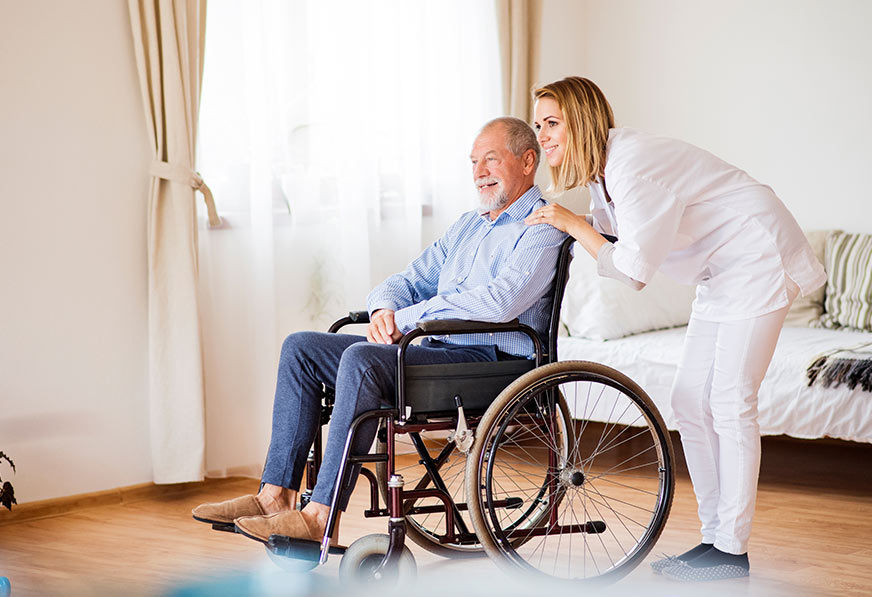 nurse aid with man in wheelchair