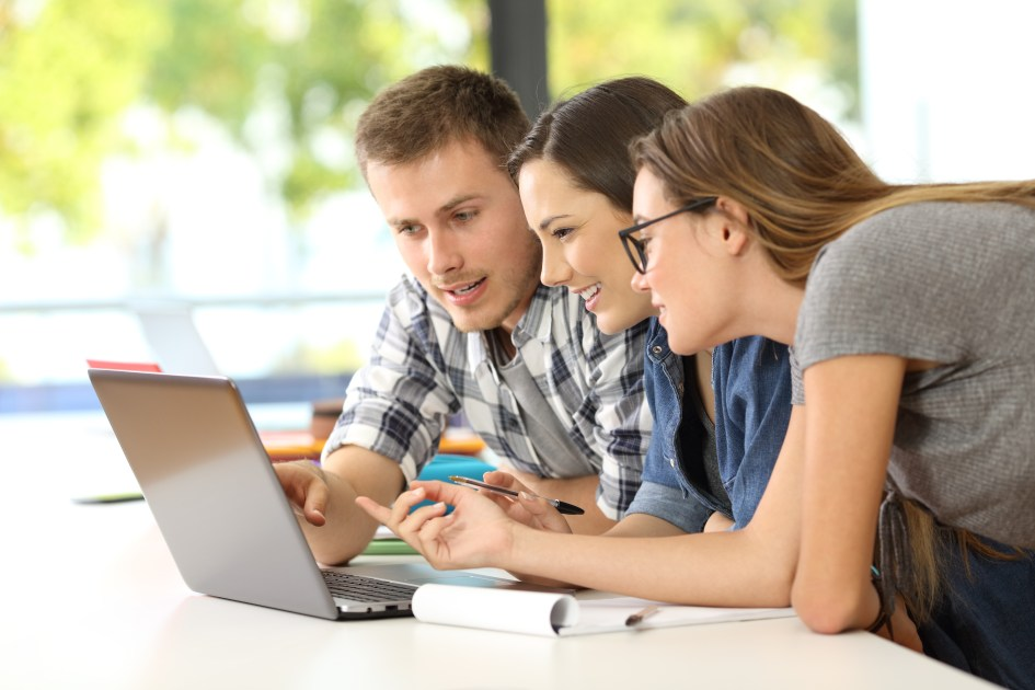 Three students learning together on line with a laptop in a classroom