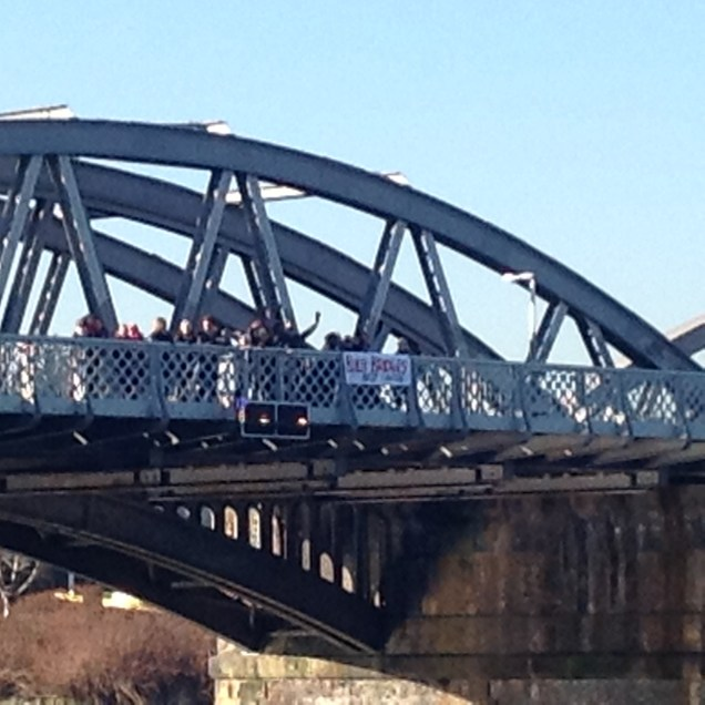 Protesters hanging a 'Build Bridges Not Walls' banner on Barnes Bridge, West London on the day of Donald Trump's Inauguration.
