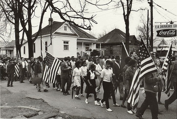 """Participants, some carrying American flags, marching in the civil rights march from Selma to Montgomery, Alabama in 1965,"" , photographer. (Peter Pettus/US Library of Congress)"