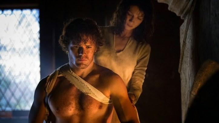 Outlander still frame of Clair bandaging Jamie's arm