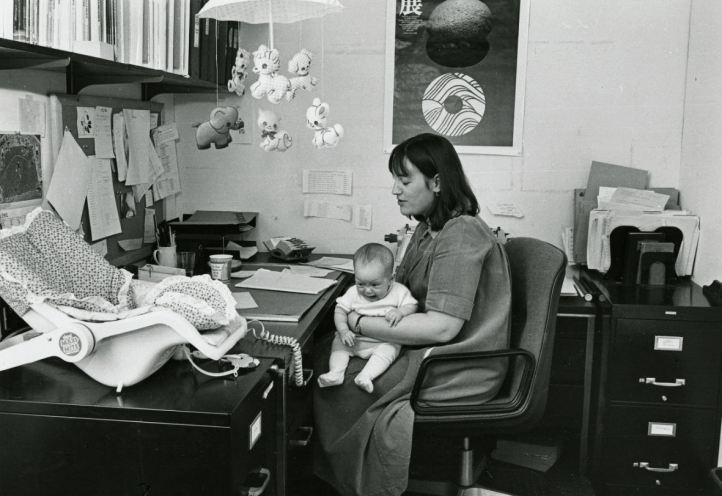 Photo of a woman with her baby at work, 1982. (Freda Leinwand/Schlesinger Library on the History of Women in America, Radcliffe Institute)