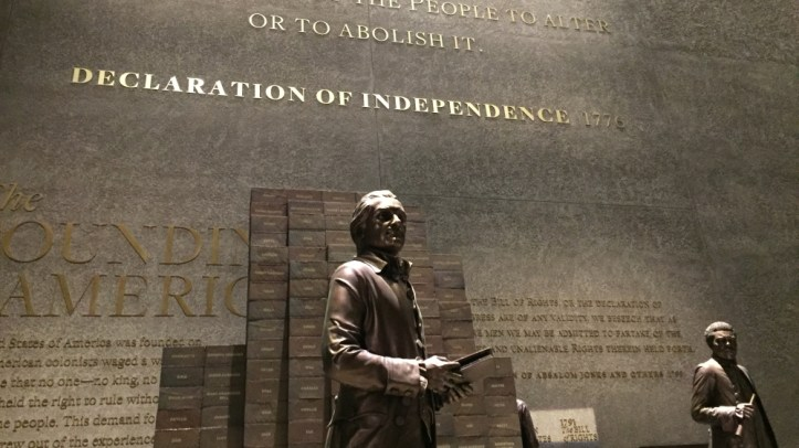 """The Thomas Jefferson """"Paradox of Liberty"""" display at the NMAAHC, featuring a statue of the third US president in front of a wall showing names of people he enslaved. (Dalia Hatuqa/Al Jazeera)"""