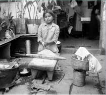 A young girl grinds maize on her family's patio. (Instituto Nacional de Antropología e Historia, Mexico)