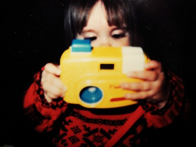 Toddler holding a yellow plastic camera.