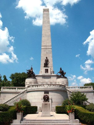 A photo of the Lincoln family tomb, featuring a tall stone obelisk behind and atop a curved stone building with three statues, the photo set against a blue sky