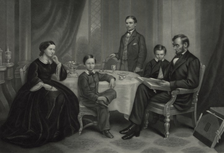 An 1861 painting of the Lincoln family in muted black and white. Abraham and Mary Todd are seated at either end of a table. Abraham is reading from a book. One son stands behind the table, one leans on Abraham's chair, and one is seated near Mary Todd looking toward the viewer