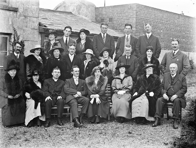 Group of white men and women are arranged int three rows, with a couple dressed in furs and finery at the front and center - this is a photograph of a 1917 wedding party in Clonmel, Ireland.